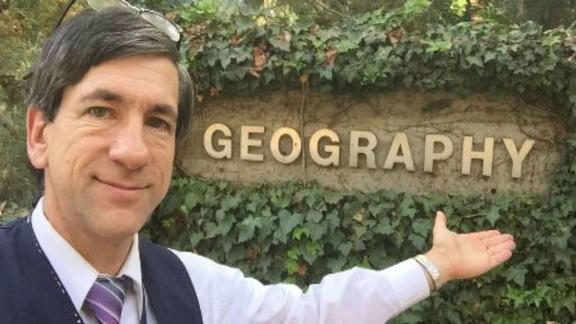 "man pointing at an outdoor sign that reads ""georgraphy"""