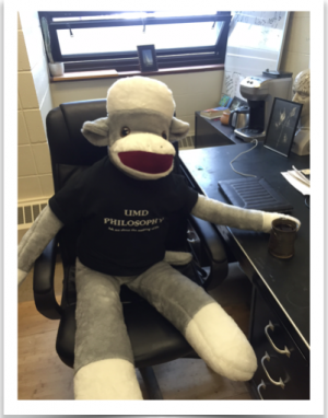A Giant stuffed sock monkey wearing a UMD Philosophy T-shirt