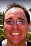 White man in glasses smiling.