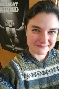 "Smiling brunette white woman in fair isle sweater standing next to a poster that reads ""Make Robot Friend, Not Robot Enemy"""