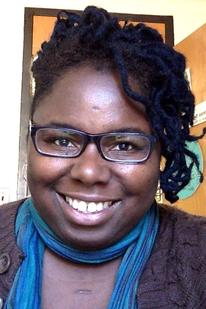 Portrait of smiling black woman wearing glasses and a green scarf.