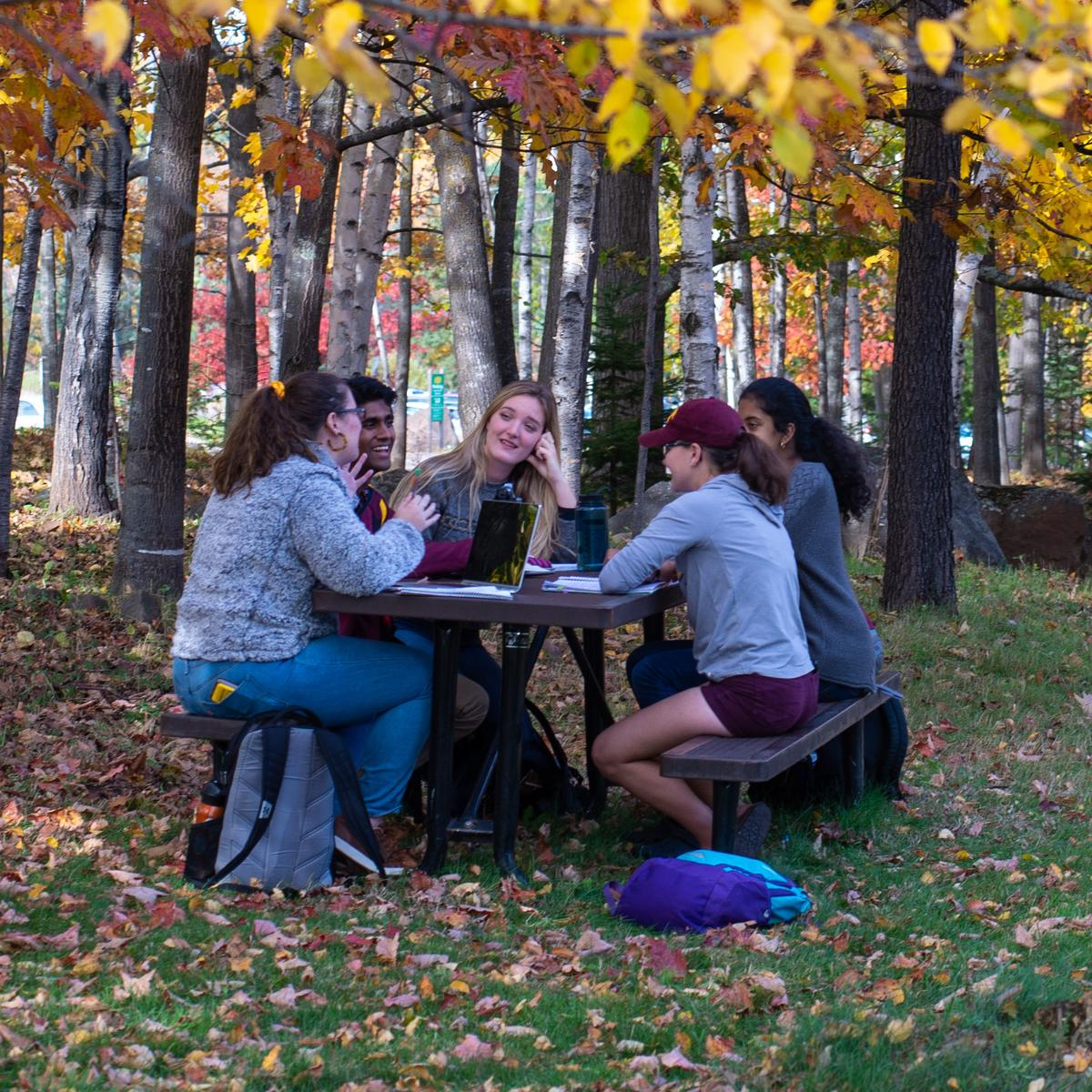 Students sitting outside at a table.
