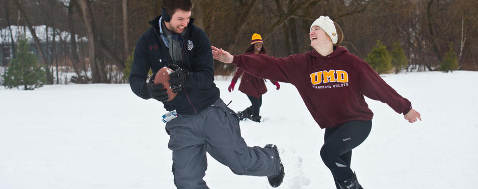 Students in the snow playing football