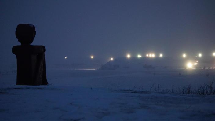 photo of sculpture overlooking industrial lights in the snow