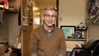 Smiling blonde man wearing glasses and sweater in an office setting.