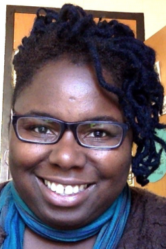 A portrait of a smiling black woman with dark dreadlocks, wearing glasses, a brown sweater, and a teal scarf.