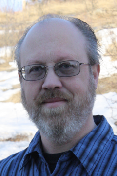A portrait of a smiling white man with a grey beard wearing glasses and a blue and black checked shirt.