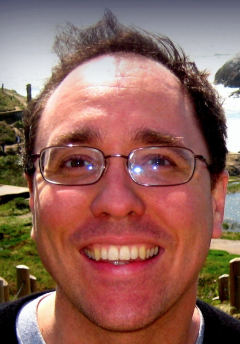 Smiling brown haired white man with glasses.