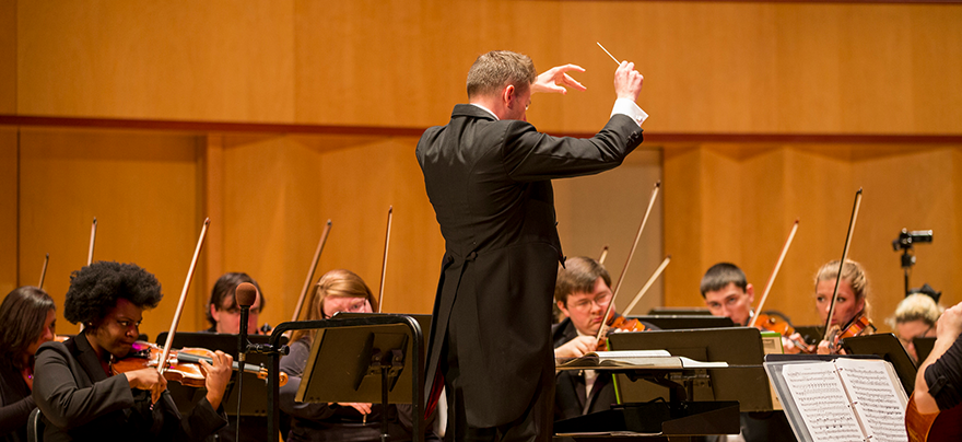 conductor conducting a group of musicians