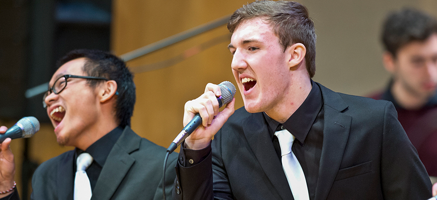 two male students singing on stage